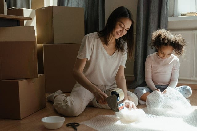 A woman and a girl trying to pack fragile items when moving.